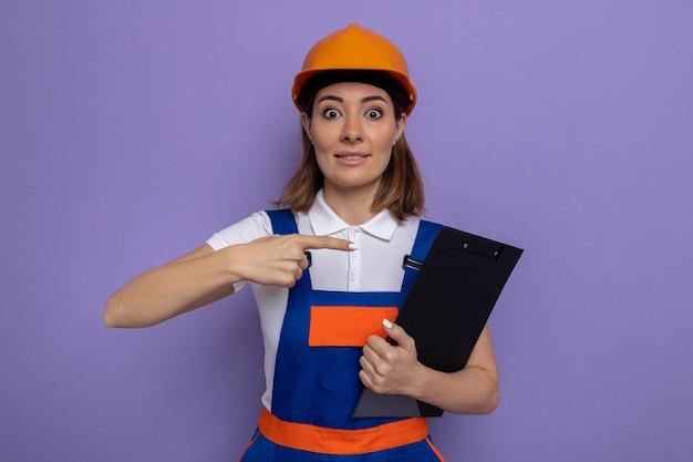 건설 유니폼을 입은 젊은 건축업자 여성과 검지 손가락으로 클립보드를 가리키는 안전 헬멧을 들고 보라색 벽 위에 놀라고 행복하게 서 있는 여성