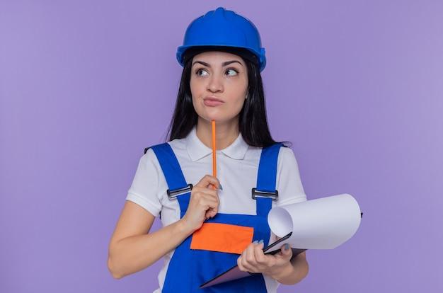 建設ユニフォームとクリップボードを保持している安全ヘルメットの若いビルダーの女性