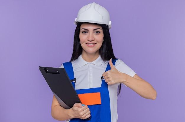 Молодая женщина-строитель в строительной форме и защитном шлеме с буфером обмена