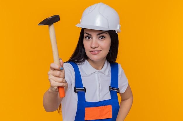 オレンジ色の壁の上に立っている顔に笑顔で正面を見てハンマーを保持している建設制服と安全ヘルメットの若いビルダーの女性