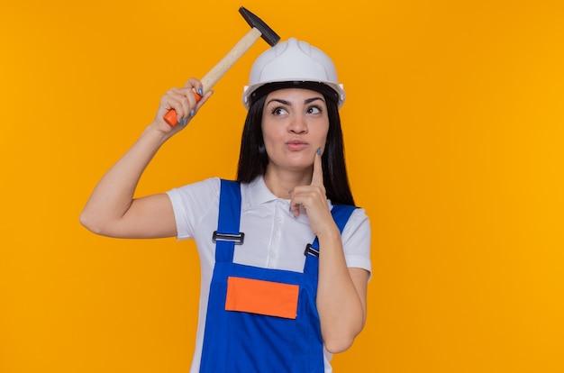 オレンジ色の壁の上に立っている顔の思考に物思いにふける表情で見上げるハンマーを保持している建設制服と安全ヘルメットの若いビルダーの女性
