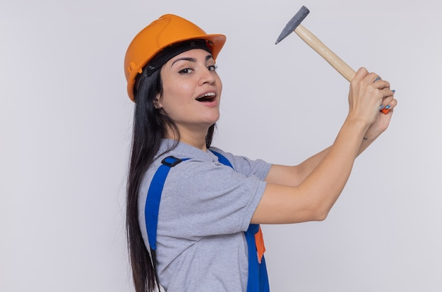白い壁の上に立っている正面を見て自信を持って笑顔のハンマーを保持している建設制服と安全ヘルメットの若いビルダーの女性