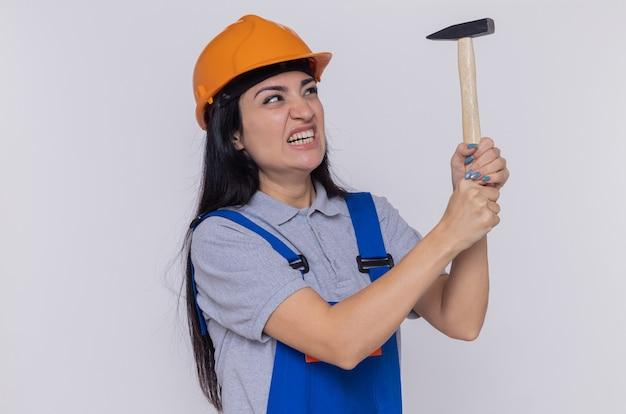 白い壁の上に立っているイライラした表情で叫んでハンマーを保持している建設制服と安全ヘルメットの若いビルダーの女性