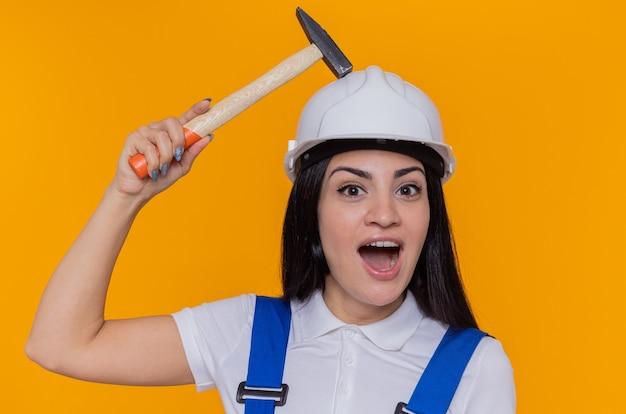 建設制服とハンマーを保持している安全ヘルメットの若いビルダーの女性