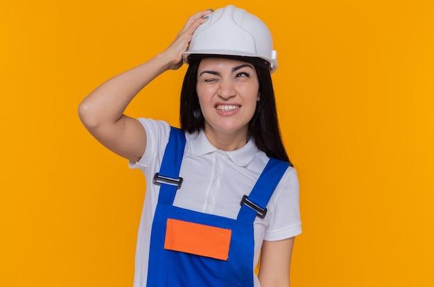 Молодая женщина-строитель в строительной форме и защитном шлеме, держащая руку на голове с раздраженным выражением лица, стоит над оранжевой стеной