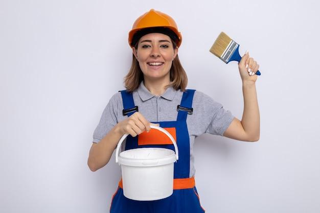 建設ユニフォームとペイントバケツとペイトブラシを保持している安全ヘルメットの若いビルダーの女性は、白い壁の上に元気に立って幸せで前向きな笑顔