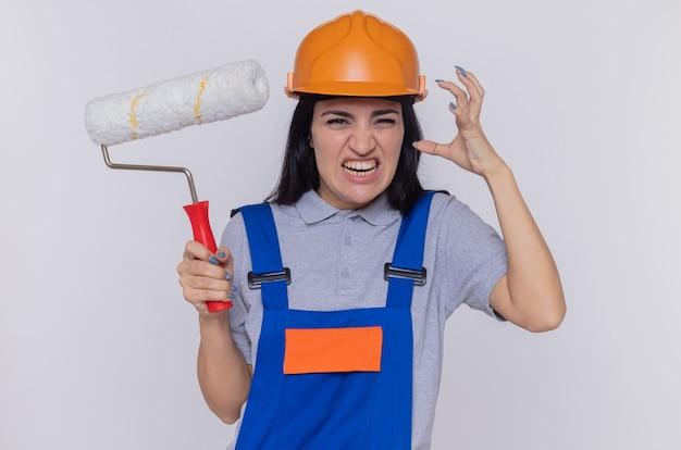 建設制服と安全ヘルメットの若いビルダーの女性は、白い壁の上に立って腕を上げて怒ってイライラして正面を見てペイントローラーを保持しています
