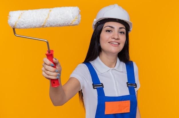 オレンジ色の壁の上に立って自信を持って笑顔の正面を見てペイントローラーを保持している建設制服と安全ヘルメットの若いビルダーの女性