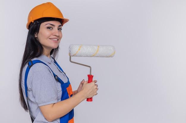 白い壁の上に立って自信を持って笑顔の正面を見てペイントローラーを保持している建設制服と安全ヘルメットの若いビルダーの女性