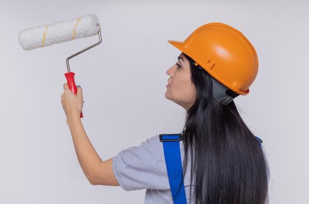 彼女の後ろの絵の壁で立っているペイントローラーを保持している建設制服と安全ヘルメットの若いビルダーの女性