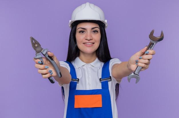 紫色の壁の上に立って自信を持って笑顔の正面を見てレンチとペンチを保持している建設制服と安全ヘルメットの若いビルダーの女性 無料写真