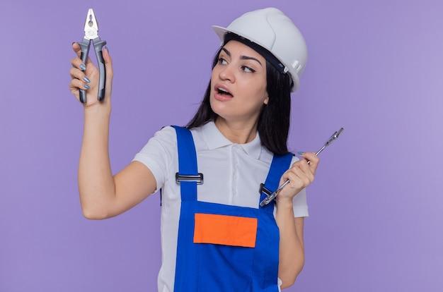 紫色の壁の上に立って選択をしようとして混乱しているように見えるレンチとペンチを保持している建設制服と安全ヘルメットの若いビルダーの女性 無料写真