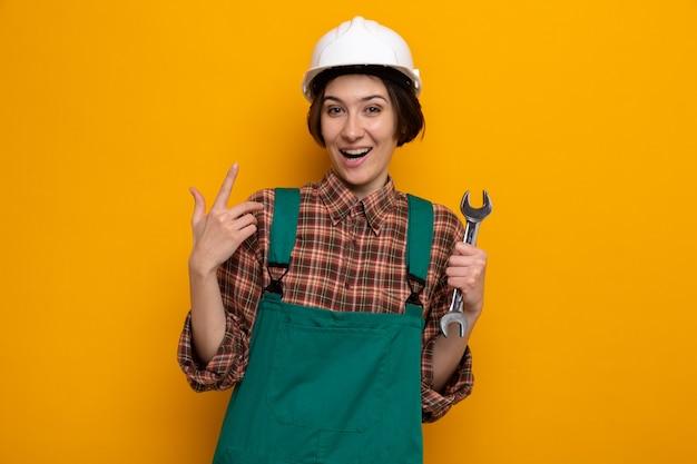 Молодая женщина-строитель в строительной форме и защитном шлеме, держащая гаечный ключ, счастлива и удивлена, показывая указательный палец, стоящий на оранжевом