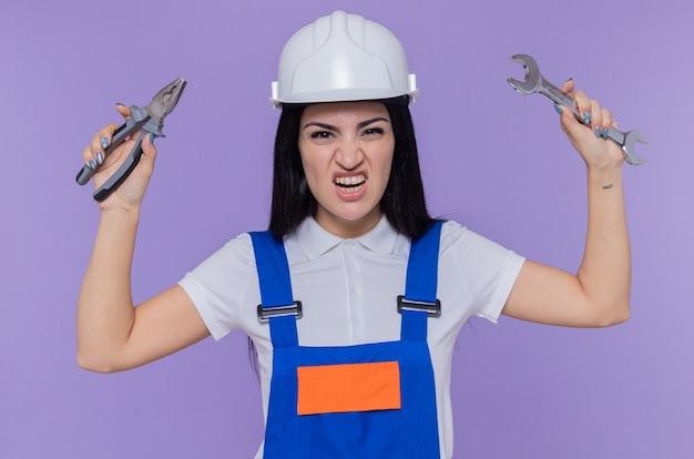紫色の壁の上に立っている怒っている顔で攻撃的な表情で正面を見てレンチを保持している建設制服と安全ヘルメットの若いビルダーの女性