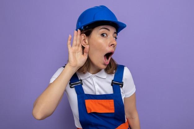 건설 유니폼과 안전 헬멧을 쓴 젊은 건축업자 여성은 보라색 벽 위에 서 있는 험담을 들으려고 귀에 손을 대고 놀라고 놀란 것처럼 보입니다.