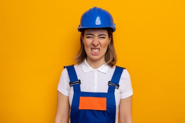 건설 유니폼과 안전 헬멧을 쓴 젊은 건축업자 여성이 짜증을 내고 짜증을 내며 오렌지 위에 서 있는 입꼬리를 찡그린다