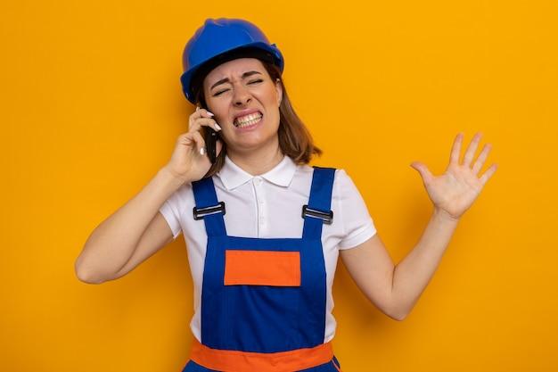 オレンジ色の上に立っている携帯電話で話している間、イライラしてイライラしているように見える建設制服と安全ヘルメットの若いビルダーの女性