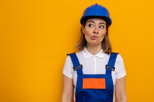 건설 유니폼과 안전 헬멧을 쓴 젊은 건축업자 여성이 주황색 벽 위에 서 있는 혼란스러운 입술을 옆으로 바라보고 있다