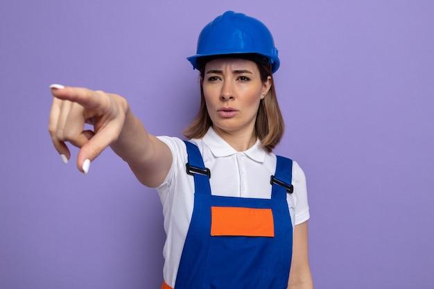 Молодая женщина-строитель в строительной форме и защитном шлеме смотрит в сторону с серьезным лицом, указывая указательным пальцем на что-то стоящее на фиолетовом