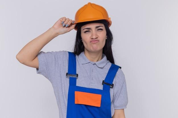 カメラを見て建設制服と安全ヘルメットの若いビルダーの女性