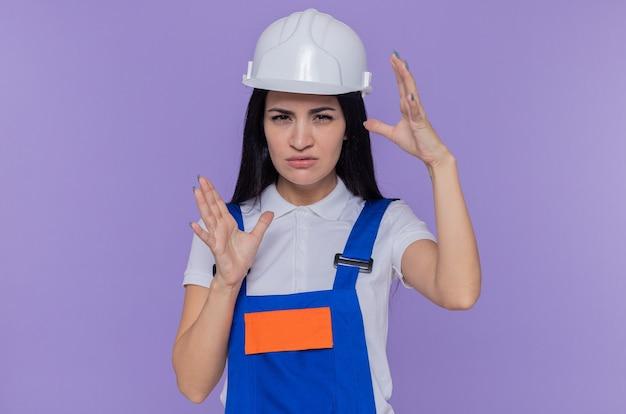 Молодая женщина-строитель в строительной форме и защитном шлеме, глядя на фронт, концентрируясь на задаче, делая жест размера руками, стоящими над фиолетовой стеной