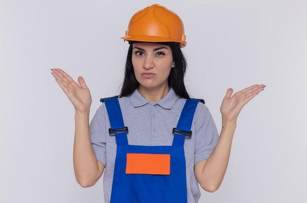 白い壁の上に立って腕を上げて混乱し、非常に心配している正面を見て建設制服と安全ヘルメットの若いビルダーの女性