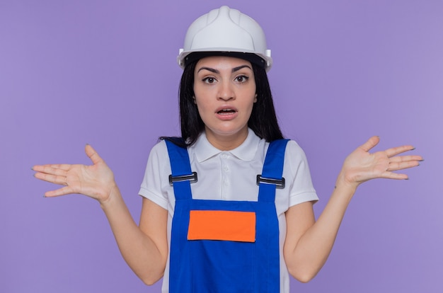 紫色の壁の上に立って腕を上げて混乱している正面を見て建設制服と安全ヘルメットの若いビルダーの女性