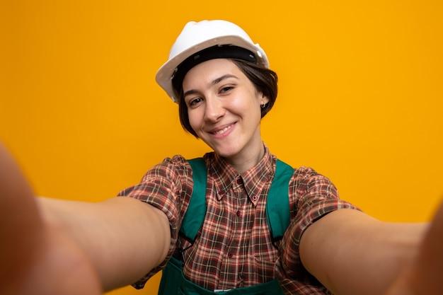건설 유니폼과 안전 헬멧을 쓴 젊은 건축업자 여성이 주황색 벽 위에 즐겁게 서서 행복하고 긍정적인 미소를 짓고 있습니다.