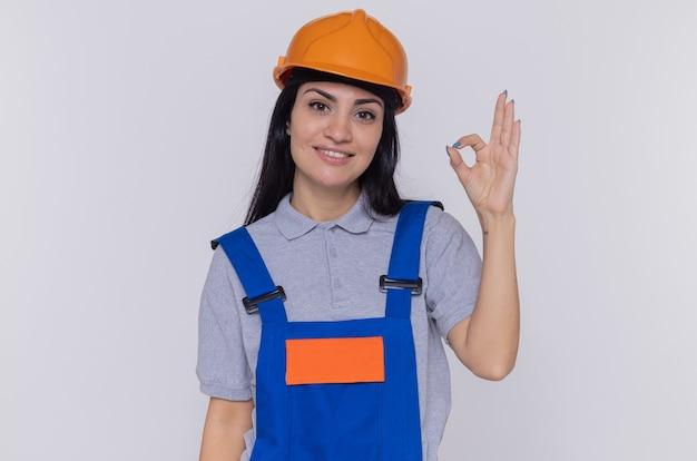 建設制服と安全ヘルメットの若いビルダーの女性は、白い壁の上に立っているokサインを示す幸せで前向きな笑顔を正面から見ています