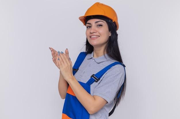 Молодая женщина-строитель в строительной форме и защитном шлеме, глядя на фронт, улыбаясь, уверенно аплодирует, стоя над белой стеной