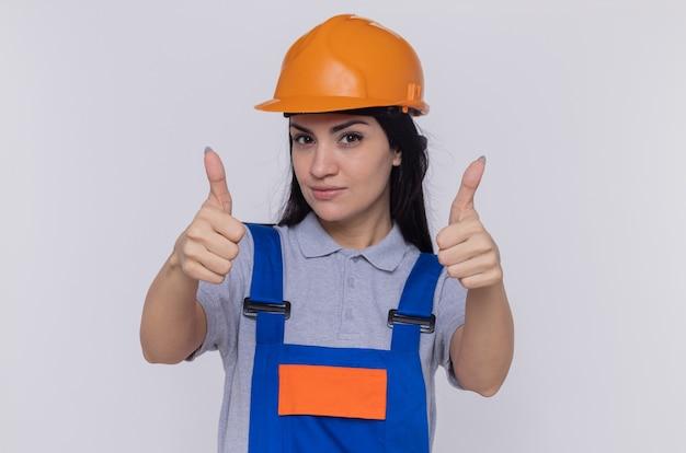 建設制服と安全ヘルメットの若いビルダーの女性は、白い壁の上に立って親指を見せて自信を持って幸せで前向きな笑顔を笑顔