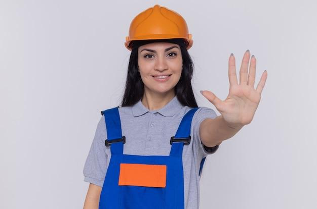 白い壁の上に立っている開いた手で停止ジェスチャーを作る自信を持って笑顔の正面を見て建設制服と安全ヘルメットの若いビルダーの女性