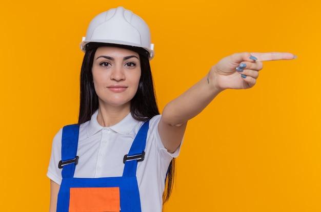 Молодая женщина-строитель в строительной форме и защитном шлеме, глядя вперед, улыбается, уверенно указывая указательным пальцем в сторону, стоящую над оранжевой стеной