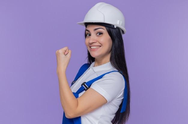 紫色の壁の上に立っている拳を見せて自信を持って笑顔の正面を見て建設制服と安全ヘルメットの若いビルダーの女性