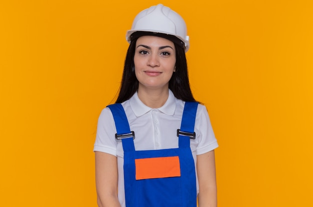 オレンジ色の壁の上に立って自信を持って笑顔の正面を見て建設制服と安全ヘルメットの若いビルダーの女性