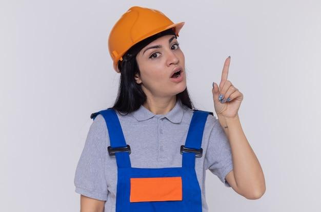 Молодая женщина-строитель в строительной форме и защитном шлеме, смотрящая вперед, удивилась, показывая указательный палец, имеющий новую хорошую идею, стоящую над белой стеной