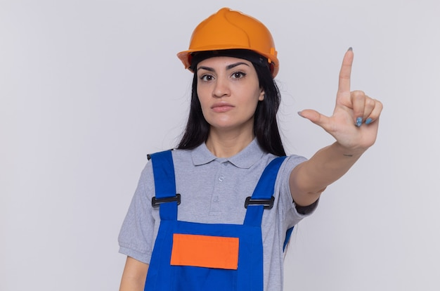白い壁の上に立っている人差し指の警告を示す深刻な顔で正面を見て建設制服と安全ヘルメットの若いビルダーの女性