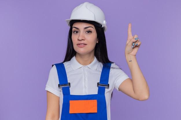 Молодая женщина-строитель в строительной форме и защитном шлеме, смотрящая вперед с улыбкой на умном лице, показывает указательный палец, имеющий отличную новую идею, стоящий над фиолетовой стеной
