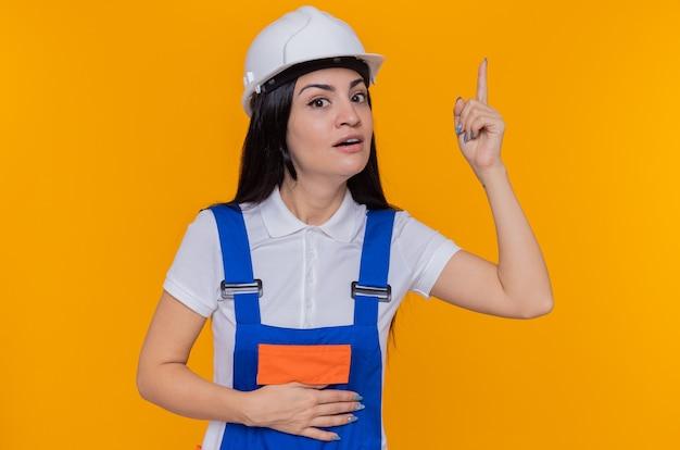 Молодая женщина-строитель в строительной форме и защитном шлеме, смотрящая вперед с улыбкой на умном удивленном лице, показывает указательный палец, имеющий отличную идею, стоящий над оранжевой стеной