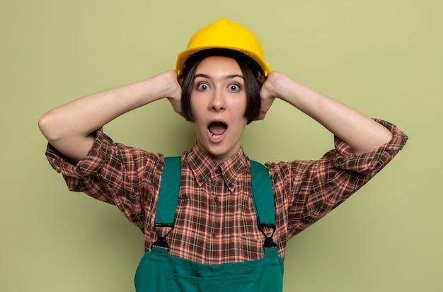 건설 유니폼과 안전 헬멧을 쓴 젊은 건축업자 여성이 앞을 바라보고 걱정하고 충격을 받아 녹색 벽 위에 공황 상태로 서 있는 그녀의 머리에 손을 잡고 충격을 받았습니다.