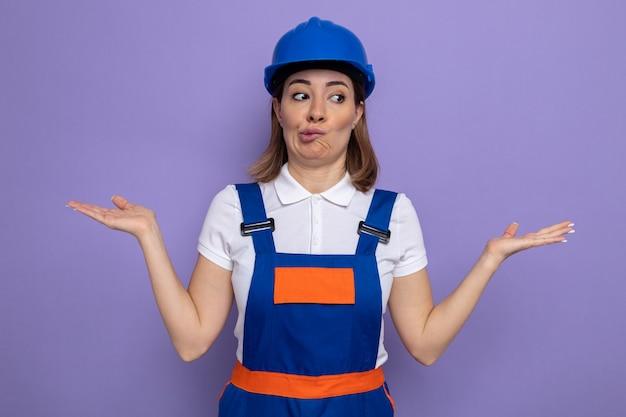 건설 유니폼을 입은 젊은 건축업자 여성과 보라색 위에 서 있는 혼란스러운 어깨를 으쓱하는 듯한 안전 헬멧