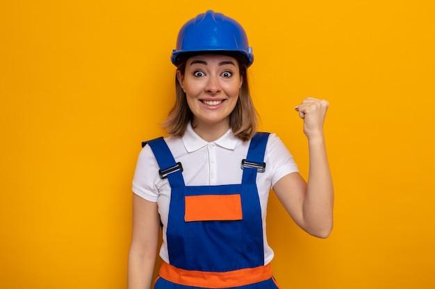 건설 유니폼과 안전 헬멧을 쓴 젊은 건축업자 여성이 승자처럼 행복하고 흥분하여 주먹을 들고 있다