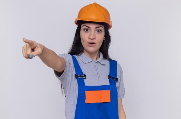 白い壁の上に立っている何かを人差し指で指して驚いて見える建設制服と安全ヘルメットの若いビルダーの女性