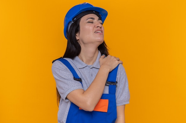 建設制服と安全ヘルメットの若いビルダーの女性は彼女の肩に触れて気分が悪い痛みを感じています
