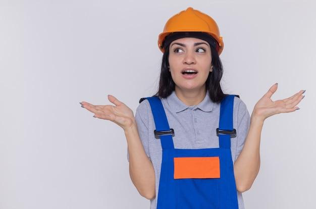 建設の制服と安全ヘルメットの若いビルダーの女性が混乱した腕を横に広げて見上げる