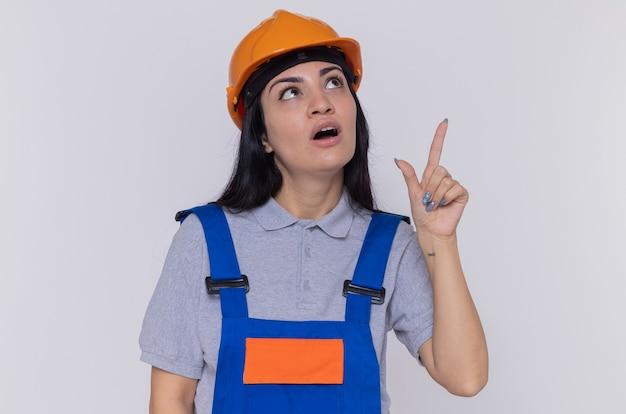 白い壁の上に立っている何かを人差し指で指して驚いて見上げる建設制服と安全ヘルメットの若いビルダー女性