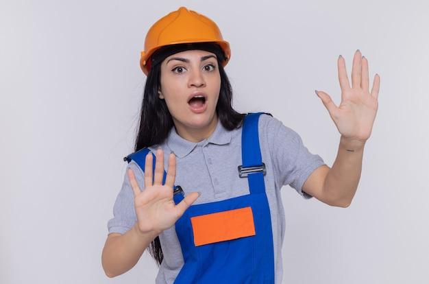建設制服と安全ヘルメットの若いビルダーの女性が心配そうに見えます
