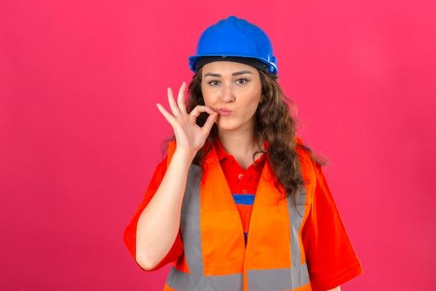 Молодой строитель женщина в строительной форме и защитный шлем, делая жест молчания, как будто закрыв рот молнией над изолированной розовой стеной