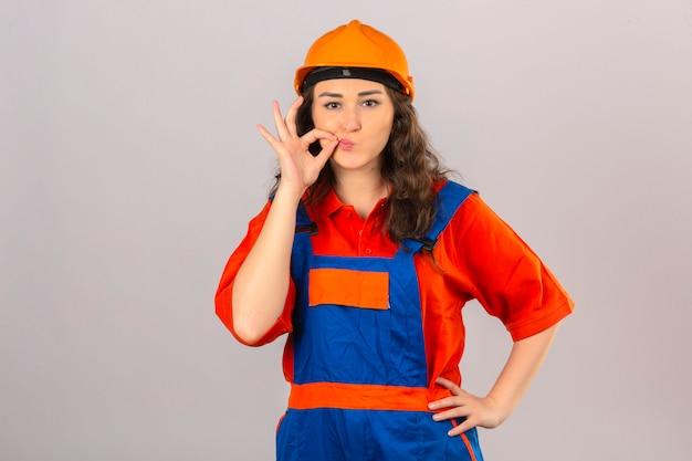 Молодая женщина строитель в строительной форме и защитный шлем, делая жест молчания, как будто закрыв рот молнией над изолированной белой стеной