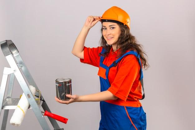 ペイントで金属製のはしごに建設の制服と安全ヘルメットの若いビルダー女性できる笑顔と分離の白い壁に彼女のヘルメットに触れる
